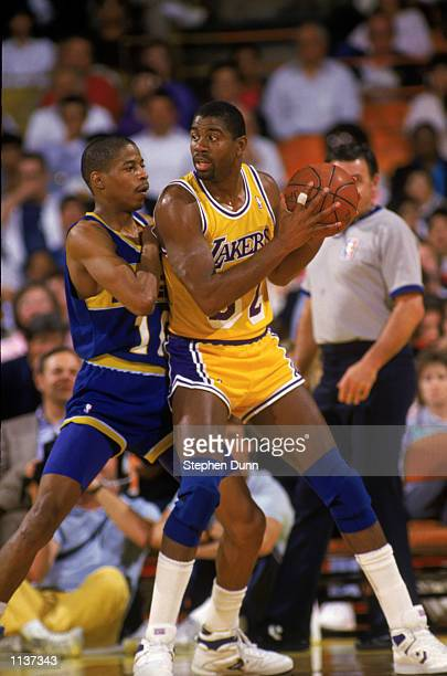 Magic Johnson of the Los Angeles Lakers holds the ball in the post during an NBA game against the Indiana Pacers at the Great Western Forum in Los...