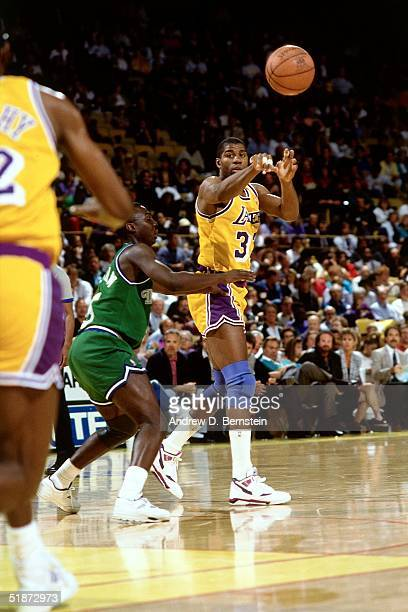 Magic Johnson of the Los Angeles Lakers makes a pass against the Dallas Mavericks during an NBA game at the Forum in Los Angeles California NOTE TO...