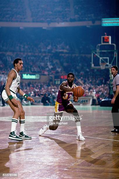 Magic Johnson of the Los Angeles Lakers passes against Dennis Johnson of the Boston Celtics during a game played circa 1985 at the Boston Garden in...