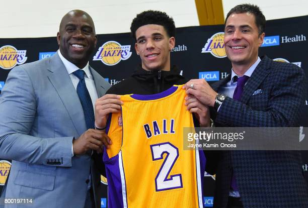 Magic Johnson president of basketball operations of the Los Angeles Lakers along with general manager Rob Pelinka present Lonzo Ball his jersey...