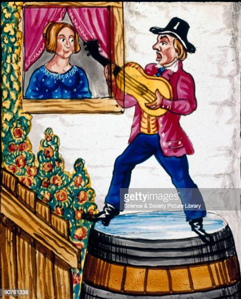 Magic lantern slide of a man serenading a woman while balancing on top of a large barrel filled with water He is playing his guitar and singing to...