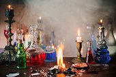Magic potion, ancient books and candles on dark background