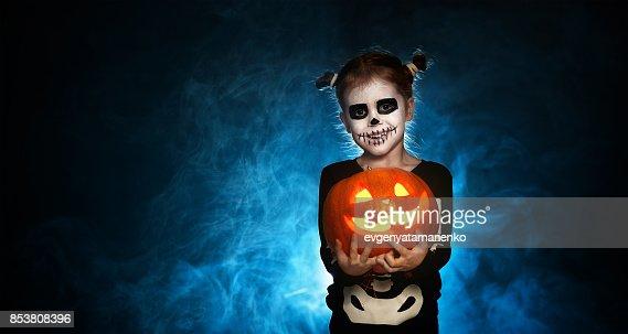 esqueleto de magia con calabaza. niña en traje para halloween : Foto de stock