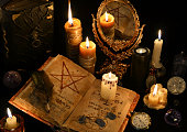 Still life with old book, ancient runes and magic mirror in candle light. Halloween concept, mystic ritual or spell with occult and esoteric symbols, divination rite. Vintage objects on table