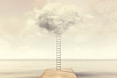 Surreal ladder rises up into the sky toward a soft cloud