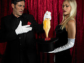 Magician and female assistant performing magic trick, frowning