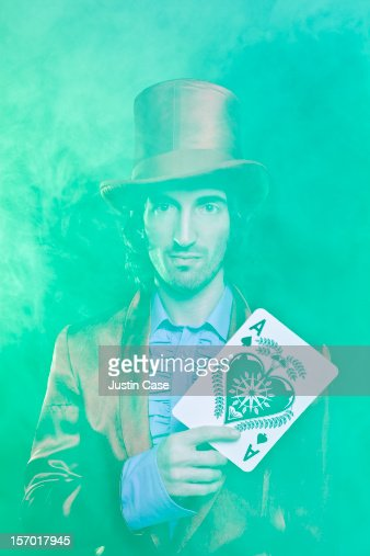 A magician holding a big ace gazing at camera : Stock Photo