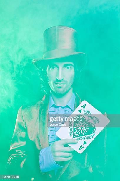 A magician holding a big ace gazing at camera