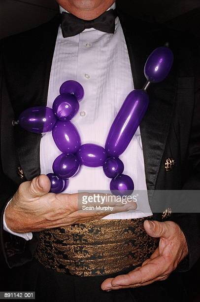 Magician holding purple balloon animal with one hand, close-up