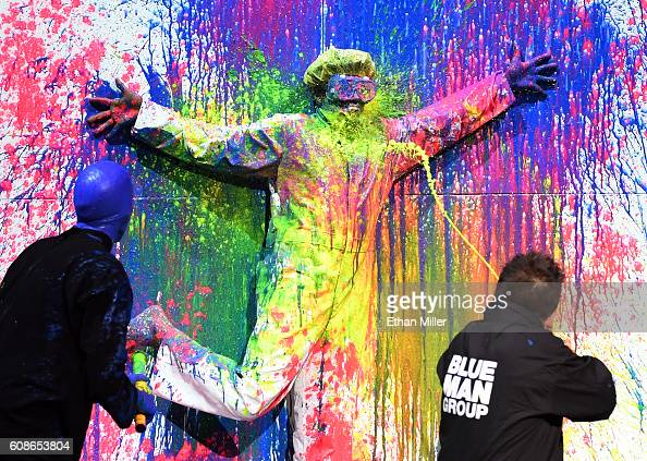 Magician Mateo Amieva shoots paint at rapper Flavor Flav as they perform with members of Blue Man Group during Criss Angel's HELP charity event at...