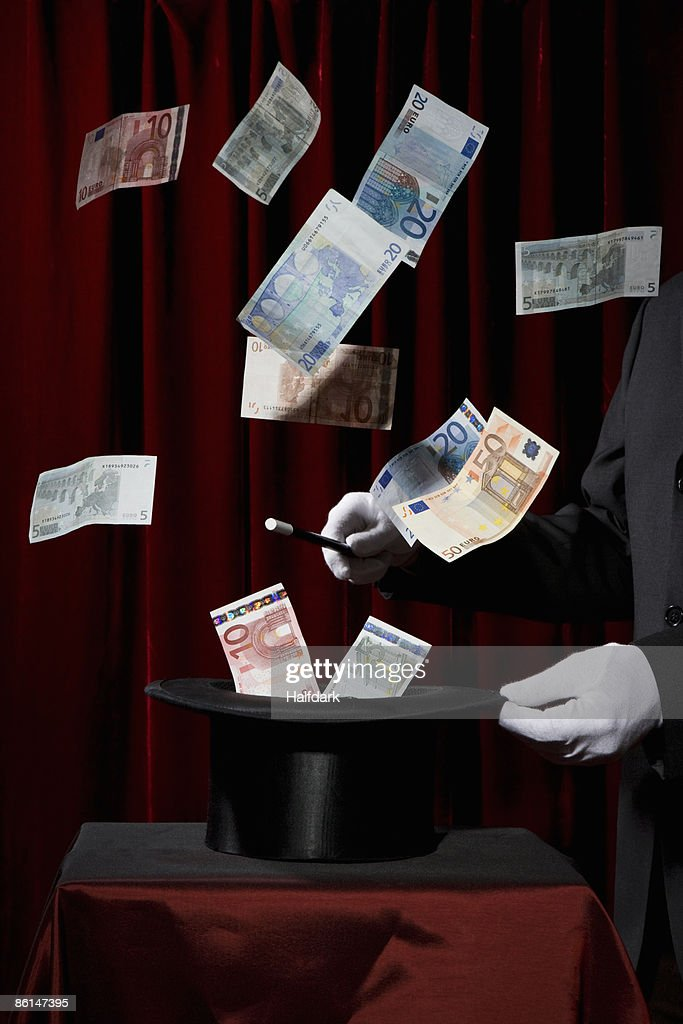 A magician performing magic by making money come out of a hat