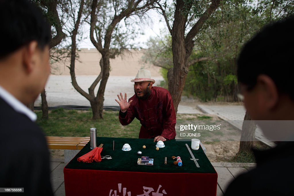 A magician performs for tourists at Jiayuguan Fort in China's northwestern Gansu province on May 15, 2013. The fort marks the first pass at the west end of China's Great Wall, and is thougt to have been built in the Ming dynasty around 1372. One of the most intact passes on the Great Wall, the fort once signified the furthest reach of China, beyond which lay the Gobi desert and the plains of central Asia. AFP PHOTO / Ed Jones