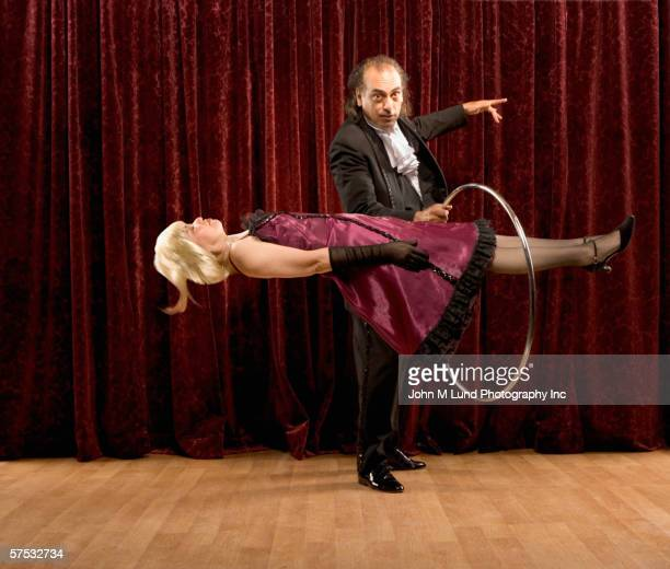 Magician putting ring around levitating woman