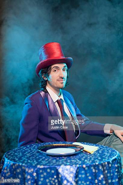 A magician sitting in front  of table
