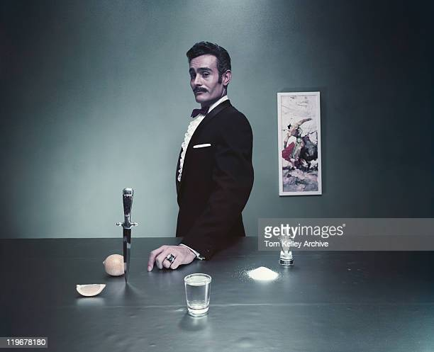 Magician standing by table with glass of water, salt and knife