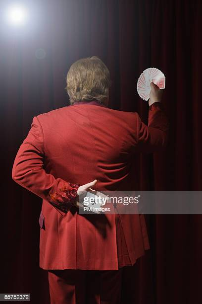 Magician with cards, rear view.