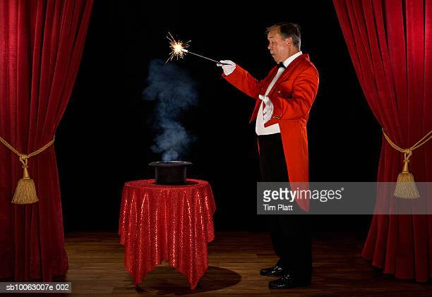 Magician with smoke in hat on stage, side view
