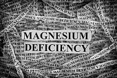 Magnesium Deficiency. Torn pieces of paper with words Magnesium Deficiency. Concept Image. Black and White. Closeup.