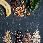 Magnesium rich food -  banana, chocolate, walnuts, cashews, chard, quinoa, beans, oatmeal, lentils. On a dark background, top view. Food background