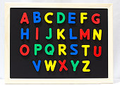 Magnet plastic alphabet on blackboard