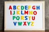 Magnet plastic alphabet on whiteboard on cement wall background