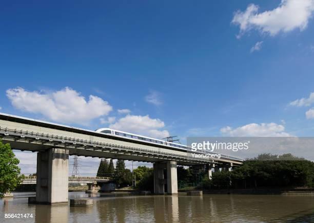 magnetic levitation (maglev) train travels at 431 km per hour through bridge shanghai, china
