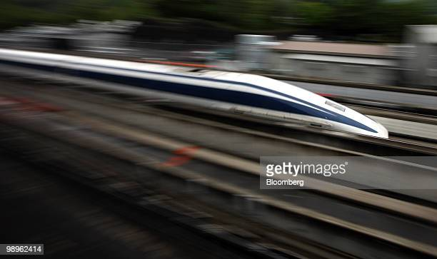 A magneticlevitation train passes at Central Japan Railway Co's Yamanashi Maglev test line in Tsuru City Yamanashi Prefecture Japan on Tuesday May 11...