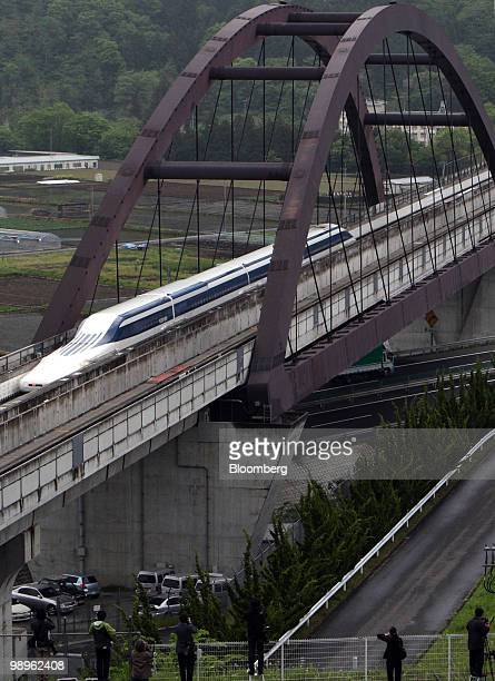 A magneticlevitation train passes over a bridge at Central Japan Railway Co's Yamanashi Maglev test line in Tsuru City Yamanashi Prefecture Japan on...