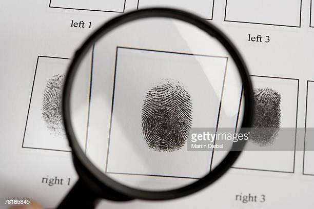 A magnifying glass above a fingerprint document