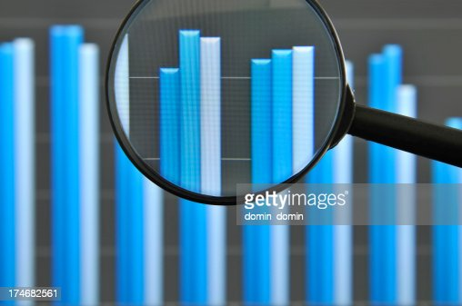 Magnifying glass and chart pictured on computer
