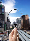 Magnifying glass and cityscape in focus, business vision and view of city