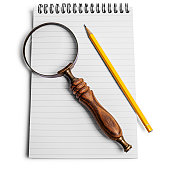 Magnifying glass and pencil and pad of paper