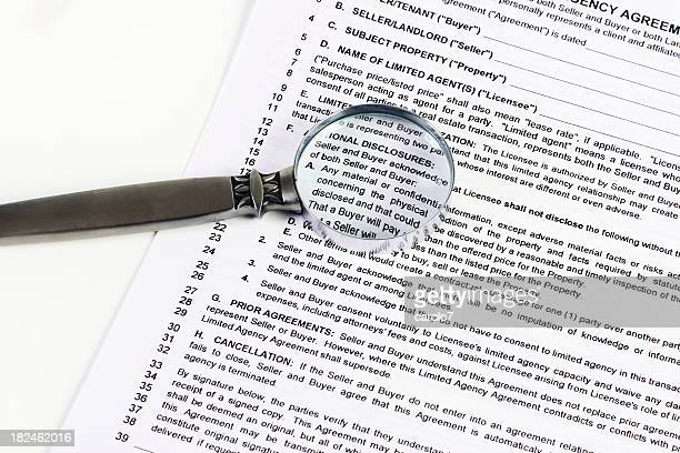 Magnifying glass close-up on buyer-seller agreement. Horizontal.