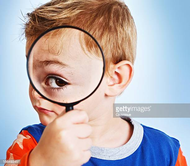 Magnifying glass enlarges playful boy's eye enormously: young Sherlock Holmes