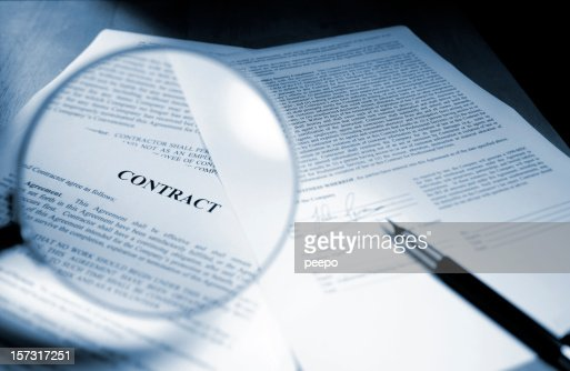 Magnifying Glass Examining Signed Legal Contract Stock Photo
