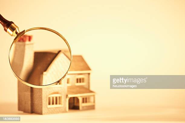 Magnifying Glass Focused on a Toy House
