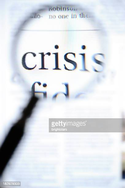 Magnifying glass focusing on crisis headlines