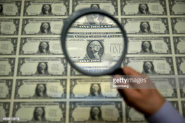 A magnifying glass is held over a 50 subject one dollar note sheet after being printed by an intaglio printing press in this arranged photograph at...