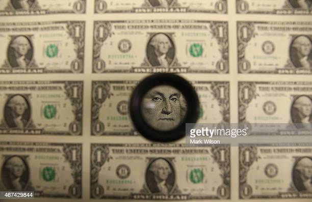 A magnifying glass is used to inspect newly printed one dollar bills at the Bureau of Engraving and Printing on March 24 2015 in Washington DC The...