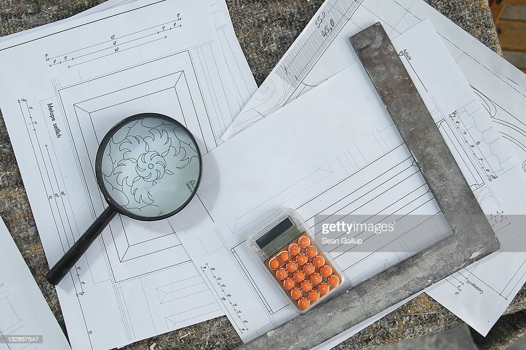 A magnifying glass lies over a technical plan showing a rosette among other tools on a sculptor's worktable at the Schlossbauhuette studio, where a team of sculptors is creating decorative elements for the facade of the Berliner Schloss city palace on November 11, 2011 in Berlin, Germany. The Berliner Schloss was the residence of the Prussian Kaiser and was among the major architectural landmarks of Berlin until it was heavily damaged by Allied bombing in 1945. The communist authorities of East Berlin demolished the building in the 1950s, and today's Berlin government is pursuing an ambitious project to rebuild the palace according to a design by Italian architect Franco Stella, which will recreate the facade of the building but with a modern interior at a cost of approximately EUR 590 million. The Humboldt Forum, the foundation leading the project, has given the Schlossbauhuette sculptors the formidable task of recreating the hundreds of architectural elements that decorated the facade, and though some original pieces were saved, more often the sculptors have only old black and white photos as reference.