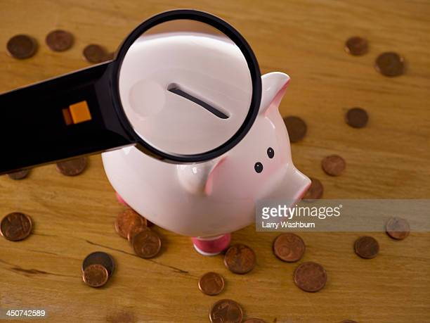 A magnifying glass magnifying the slot on a piggy bank, coins around it
