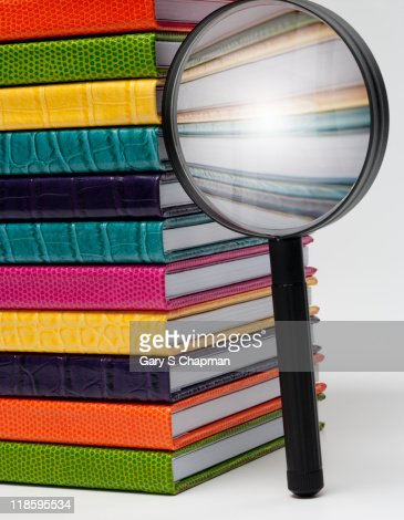 Magnifying glass next to colorful books : Stock Photo