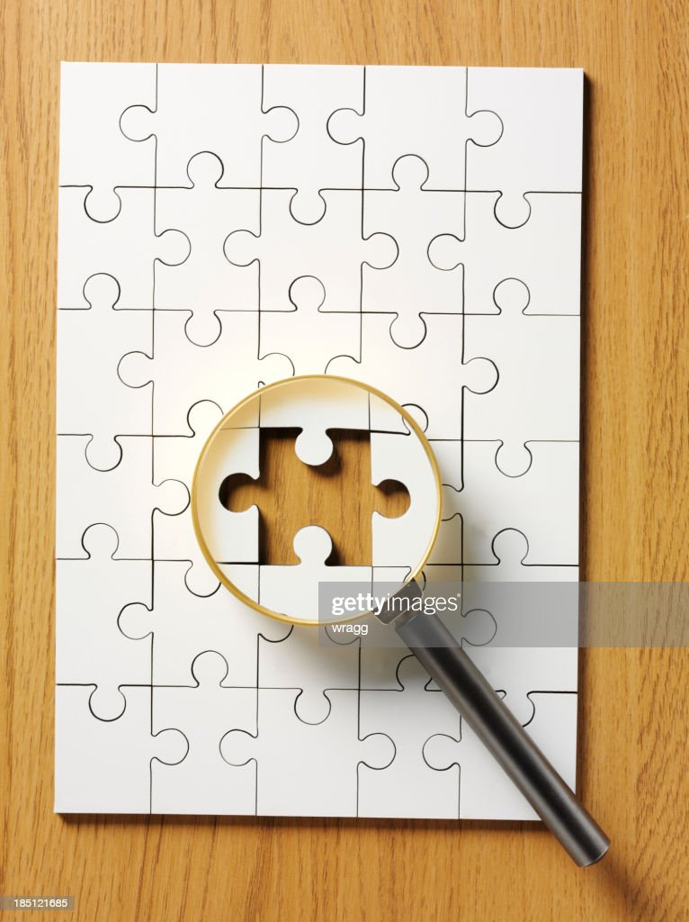 Magnifying Glass on a Jigsaw Puzzle : Stock Photo