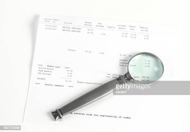 Magnifying glass on medical bill.