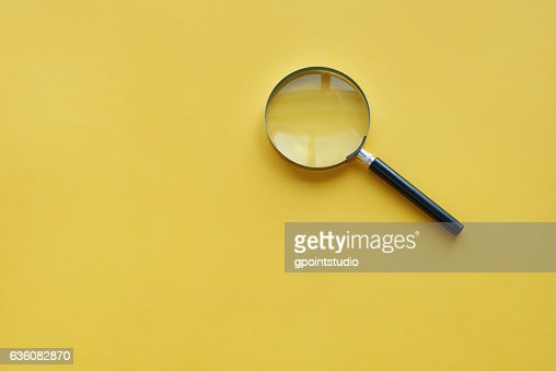 Magnifying glass on the orange background : Foto de stock