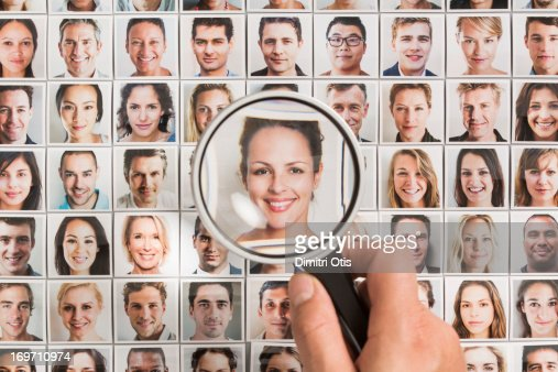 Magnifying glass on woman portrait amongst others