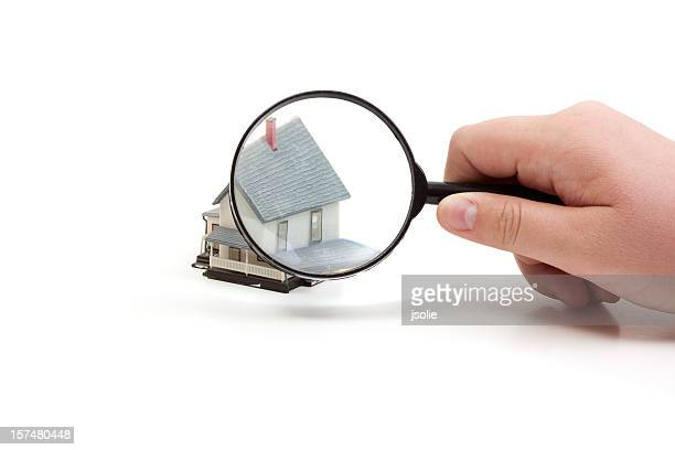 Magnifying glass over a toy house