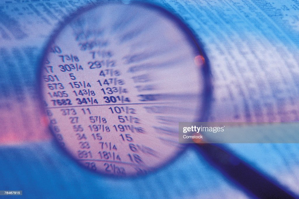 Magnifying glass over newspaper stock market figures