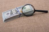 Magnifying glass  over the banknote bundle of US dollar