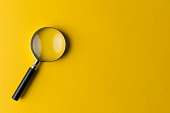 Magnifying glass on the yellow background.